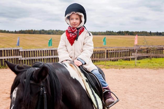 Mała dziewczynka na koniu w gospodarstwie