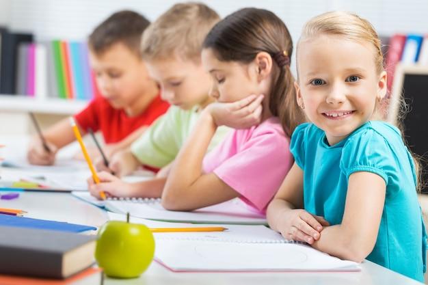 Mała dziewczynka na lekcji malarstwa w szkole z zamazanymi chłopcami na tle