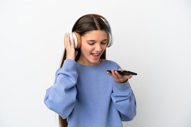 Mała dziewczynka na odosobnionym białym tle słuchająca muzyki za pomocą telefonu komórkowego i śpiewająca
