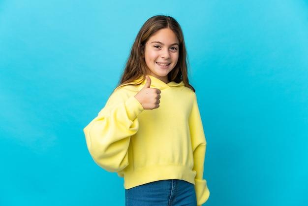 Mała dziewczynka na odosobnionym niebieskim tle, dając kciuk w górę gestu