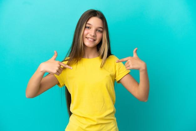 Mała dziewczynka na odosobnionym niebieskim tle dumna i zadowolona z siebie