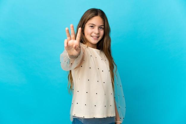 Mała dziewczynka na odosobnionym niebieskim tle szczęśliwa i licząca trzy palcami