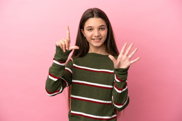 Mała dziewczynka na odosobnionym różowym tle, licząc siedem palcami