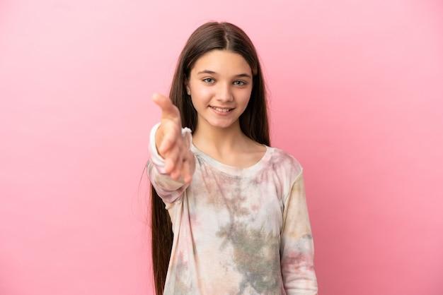 Mała dziewczynka na odosobnionym różowym tle, ściskając ręce, aby zamknąć dobrą ofertę