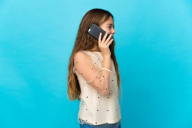 Mała dziewczynka na pojedyncze niebieskie prowadzenie rozmowy z telefonem komórkowym z kimś