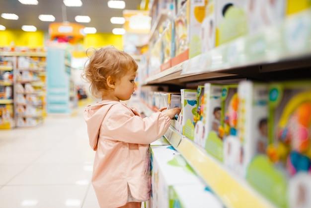 Mała dziewczynka na półce wybiera zabawki w sklepie dla dzieci, widok z boku.