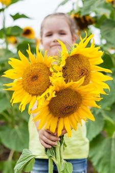 Mała dziewczynka na polu z słoneczniki. natura