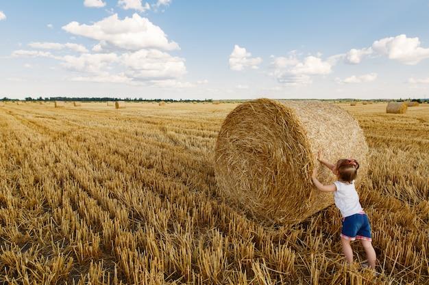 Mała dziewczynka na pszenicznym polu w lecie na słonecznym dniu. portret zabawnej małej dziewczynki na zewnątrz w wiosce na lato