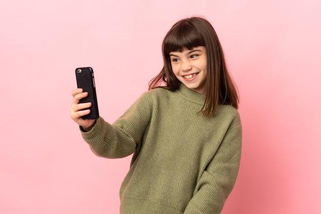 Mała dziewczynka na różowym tle dokonywanie selfie