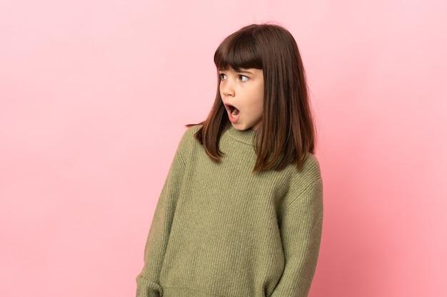 Mała dziewczynka na różowym tle robi gest niespodzianki, patrząc w bok