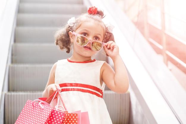 Mała dziewczynka na schodach ruchomych w centrum handlowym z zakupami