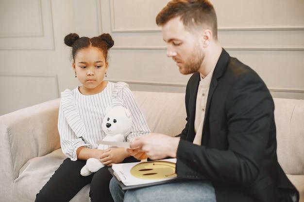 Mała dziewczynka na sesji z pschoterapeutą. mężczyzna daje test ze zdjęciami i rozmawia z uczennicą. dzieciństwo.