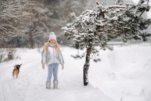 Mała dziewczynka na spacerze z psem w zimowym lesie. właścicielka i pies bawią się w zaśnieżonym lesie