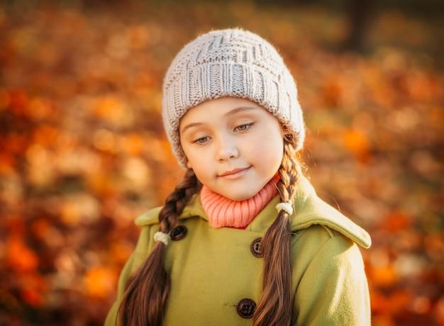 Mała dziewczynka na tle liści jesienią. smutny
