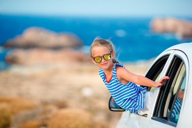 Mała dziewczynka na urlopowej podróży samochodowym tła pięknym krajobrazem