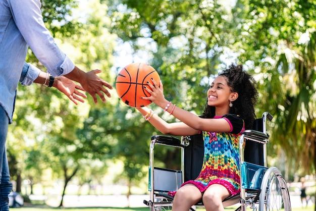 Mała dziewczynka na wózku inwalidzkim, zabawy z ojcem podczas wspólnej gry w koszykówkę w parku