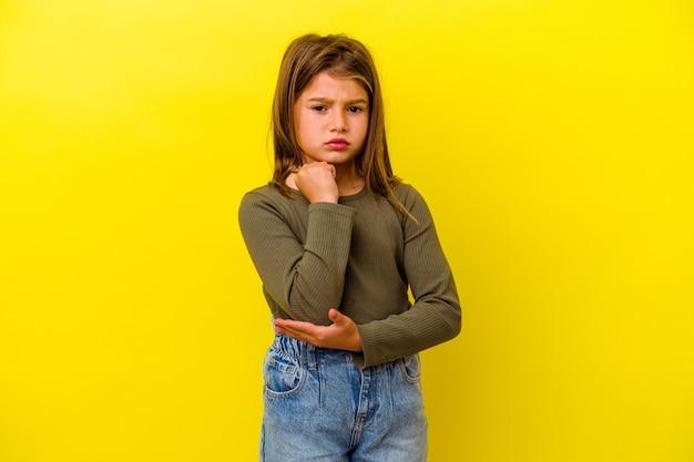 Mała dziewczynka na żółtej ścianie masuje łokieć, cierpi po złym ruchu