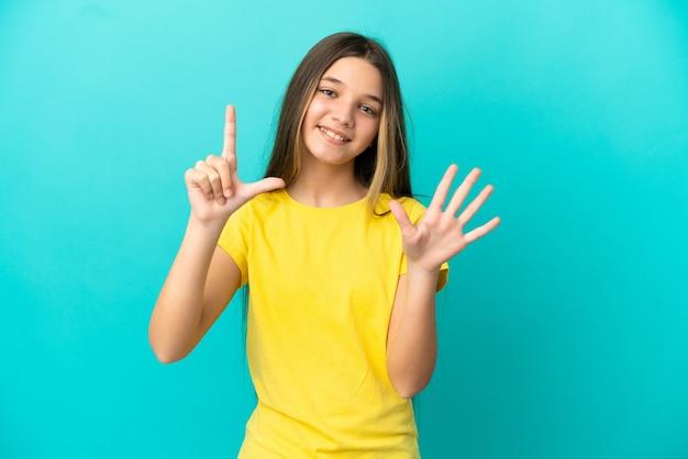 Mała dziewczynka nad odosobnioną niebieską ścianą, licząc siedem palcami