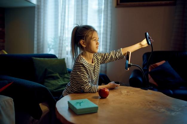 Mała dziewczynka nagrywa vlog na aparacie telefonu, vlogger dziecięcy. blogowanie dzieci w domowym studio, media społecznościowe dla młodych odbiorców, transmisja internetowa online,