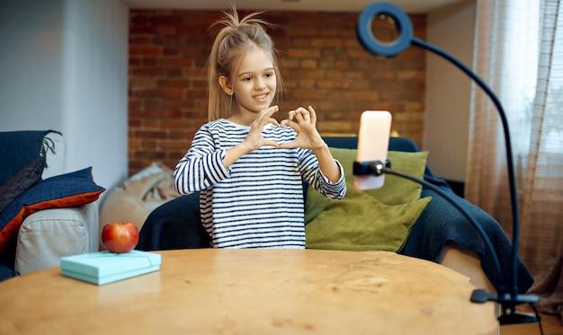 Mała dziewczynka nagrywa vloga aparatem w telefonie, blogerka dziecięca. blogowanie dzieci w domowym studio, media społecznościowe dla młodych odbiorców, transmisja internetowa online,