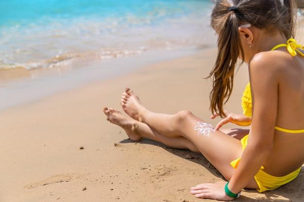Mała dziewczynka nakłada krem do opalania na kształt słońca na nogę plaży