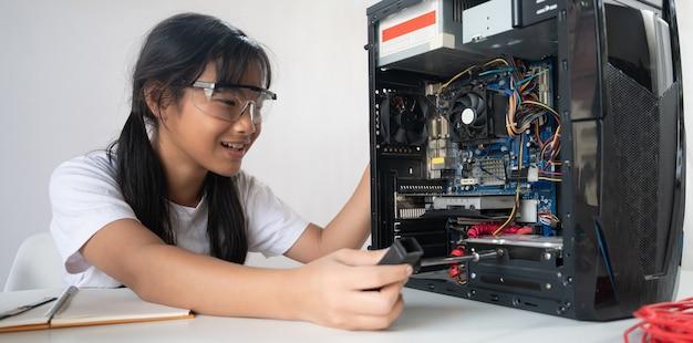 Mała dziewczynka naprawia sprzęt komputerowy przy białym stole roboczym.