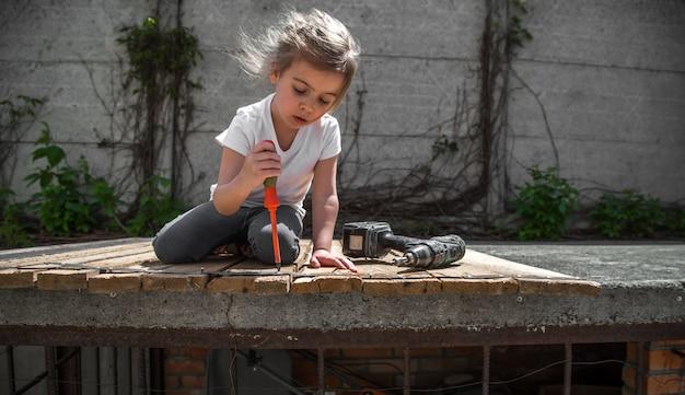 Mała dziewczynka naprawy za pomocą śrubokręta i śrubokręta w ręku