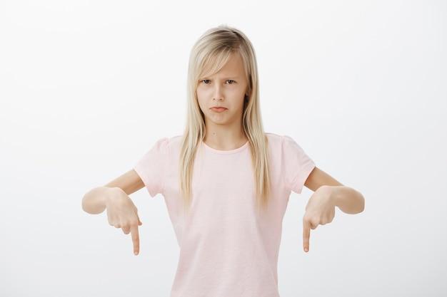 Mała dziewczynka nienawidzi mycia naczyń. portret niezadowolonej zniesmaczonej uroczej córki o blond włosach, wskazującej w dół i marszczącej brwi, obrażonej, wyrażającej niechęć i irytację na szarej ścianie