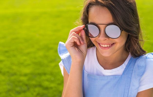 Mała dziewczynka nosi okulary przeciwsłoneczne