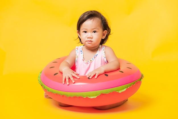 Mała dziewczynka nosi strój kąpielowy siedzi w nadmuchiwanym pierścieniu arbuza