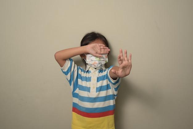 Mała dziewczynka nosząca maskę medyczną cierpiąca na zastraszanie unosi dłoń, prosząc o powstrzymanie przemocy