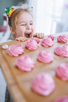 Mała dziewczynka o blond włosach i niebieskich oczach patrzy na pyszne domowe różowe pianki ot zephyr na stole w kuchni.