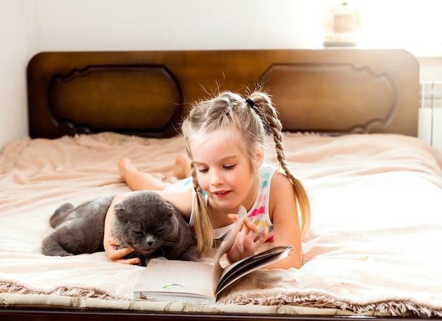 Mała dziewczynka o blond włosach leży na łóżku w domu z kotem czytającym książkę. zostań w domu. edukacja domowa dla dzieci.