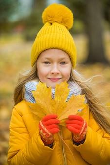 Mała dziewczynka o blond włosach w jesień parku z żółtym liściem