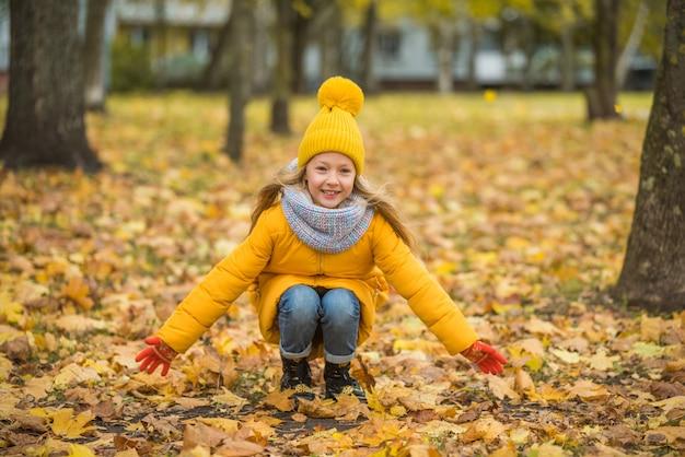 Mała dziewczynka o blond włosach w jesień parku