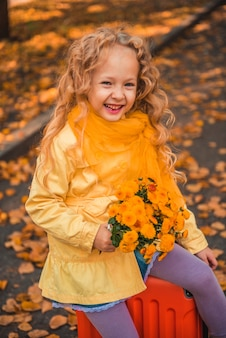 Mała dziewczynka o blond włosach w jesień tło z kwiatami i walizką
