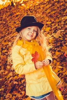 Mała dziewczynka o blond włosach w tle jesień z żółtym liściem