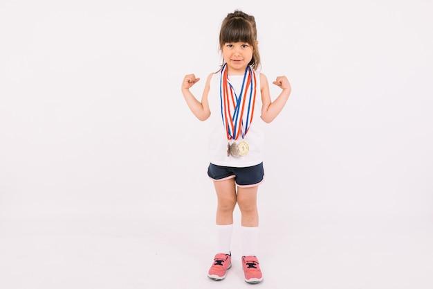 Mała dziewczynka o brązowych włosach z medalami mistrza sportu na szyi, które są symbolem siły. koncepcja sportu i zwycięstwa