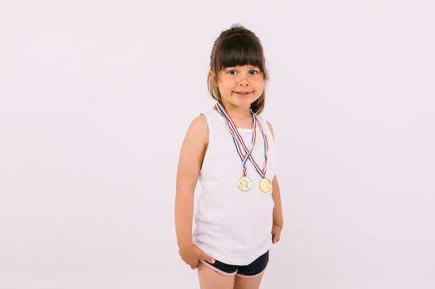 Mała dziewczynka o ciemnych włosach z medalami mistrza sportu. koncepcja sportu i zwycięstwa