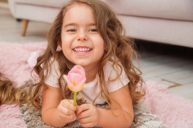 Mała dziewczynka o kaukaskim wyglądzie leży na podłodze w jasnym salonie w stylu skandynawskim i uśmiecha się trzymając w dłoni prezentowanego jej tulipana