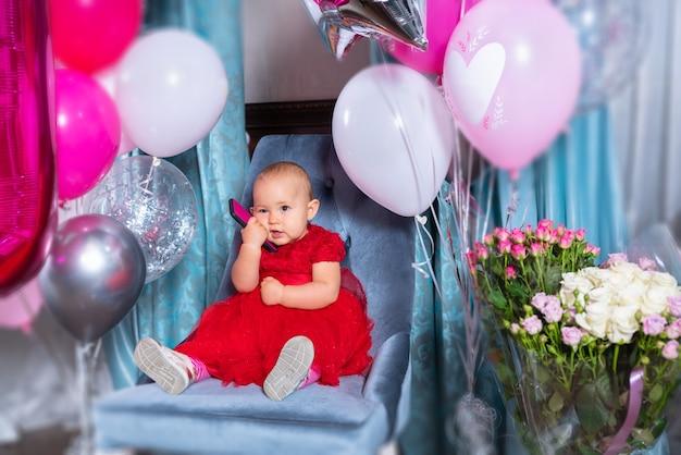 Mała dziewczynka obchodzi swoje pierwsze urodziny siedzi na krześle w czerwonej sukience