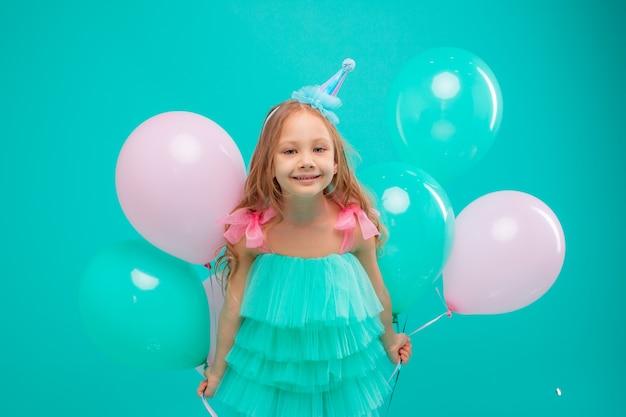 Mała dziewczynka obchodzi urodziny na turkusowym tle