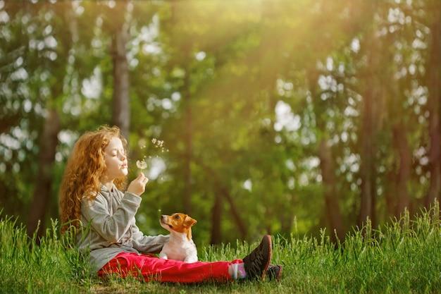 Mała dziewczynka obejmuje jego psa i dmuchania dandelion.