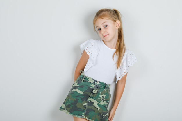 Mała dziewczynka odchylona do tyłu na ścianie w białej koszulce, spódnicy i słodko wyglądająca