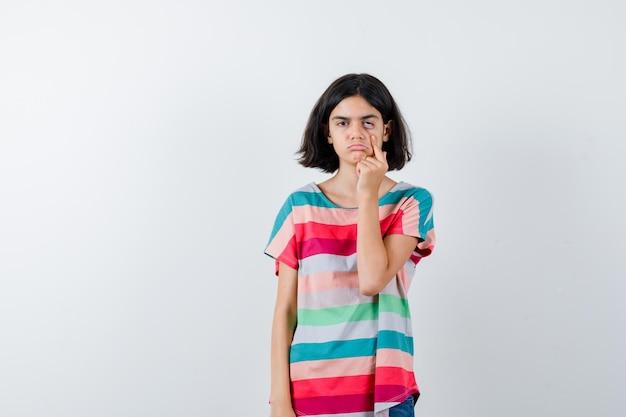 Mała dziewczynka odciąga powiekę w t-shirt i wygląda na zmęczoną. przedni widok.