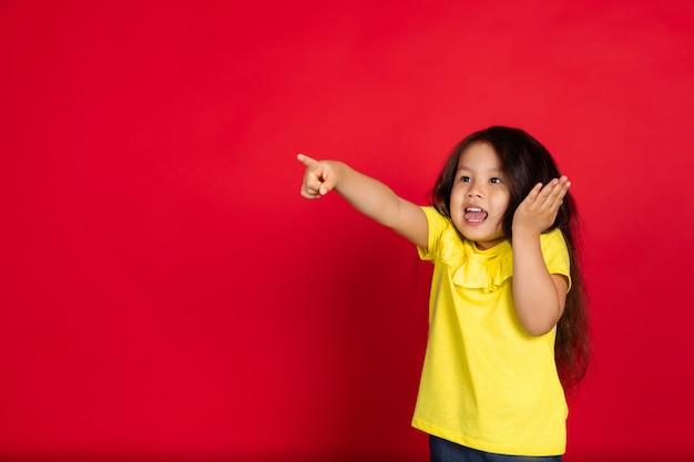 Mała dziewczynka odizolowana na czerwono, szczęśliwa
