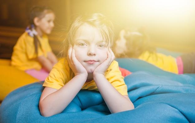 Mała dziewczynka odpoczywa na torbie na krzesło i patrząc na kamery w centrum rozrywki dla dzieci