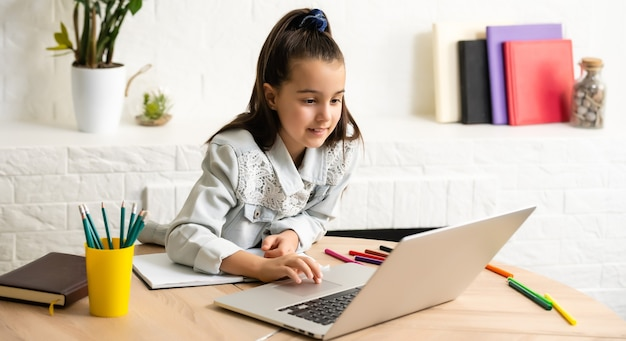 Mała dziewczynka odrabia lekcje w domu za pomocą laptopa