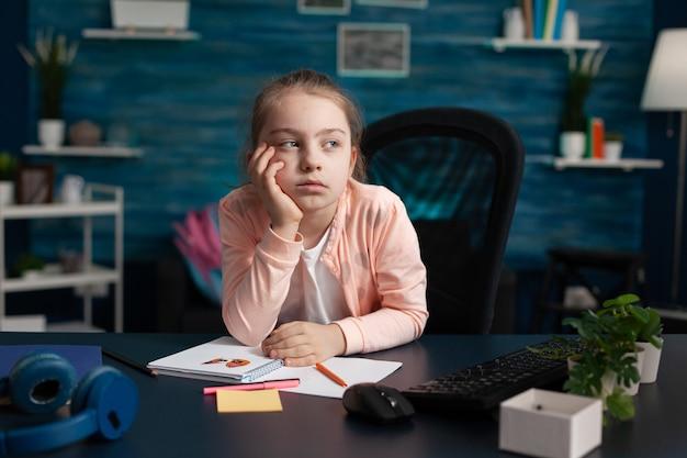 Mała dziewczynka odrabia pracę domową, czuje się znudzona i smutna