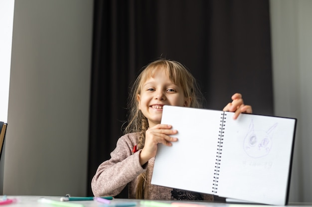 Mała dziewczynka odrabia pracę domową do szkoły podstawowej.